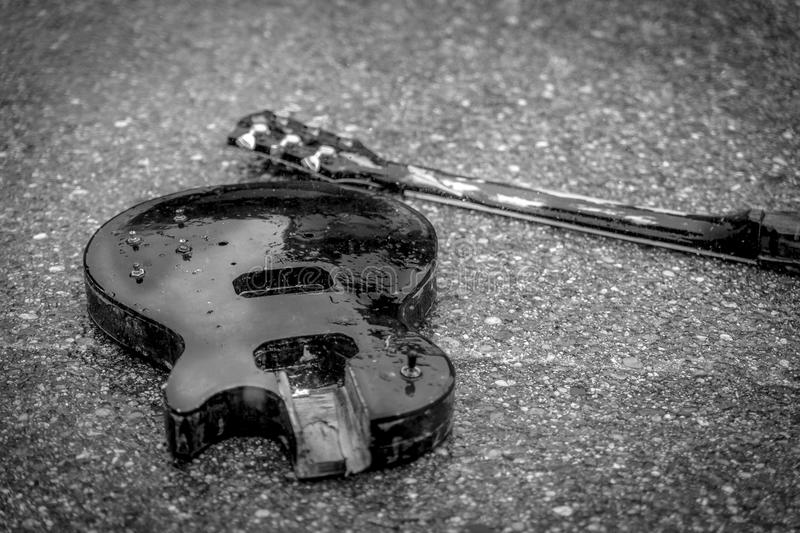 broken-electric-guitar-wet-asphalt-85006971.jpg
